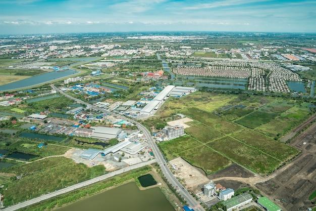 Widok na zielone pola i farmę i centrum miasta w środku tajlandii. strzał z samolotu odrzutowego.