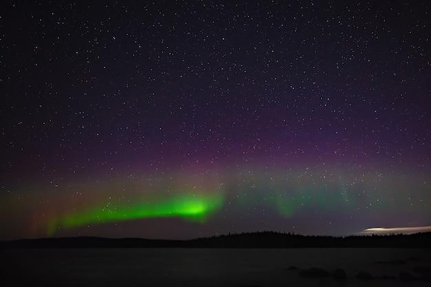 Widok na zorzę polarną. światła polarne w nocy gwiaździste niebo nad jeziorem.