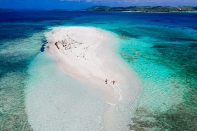 Widok nagiej wyspy z nieba. mężczyzna relaksuje brać sunbath na plaży. fotografia brać z trutniem nad piękna scena. koncepcja podróży, przyrody i krajobrazów morskich