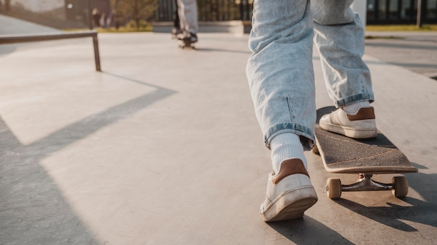 Widok nastolatka z deskorolką i miejscem na kopię w skateparku z tyłu