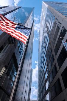Widok niektórych budynków w chicago z amerykańską flagą na niebie, illinois, stany zjednoczone ameryki
