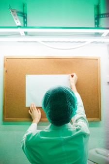 Widok nierozpoznawalnej kobiety lekarz przypinający pusty znak na tablicy ogłoszeń w laboratorium oświetlone zielonym światłem z tyłu