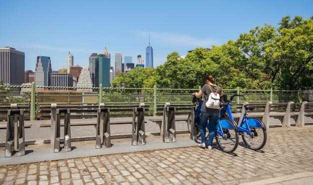 Widok nierozpoznawalnej kobiety z plecakiem na rowerze przed panoramą manhattanu w nowym jorku z tyłu