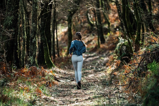 Widok nierozpoznawalnej sprawnej kobiety w sportowym stroju z tyłu biegnącej szlakiem w zielonym lesie