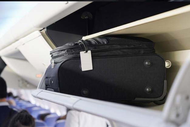 Widok niesie bagaż na górnej półce w kabinie samolotu
