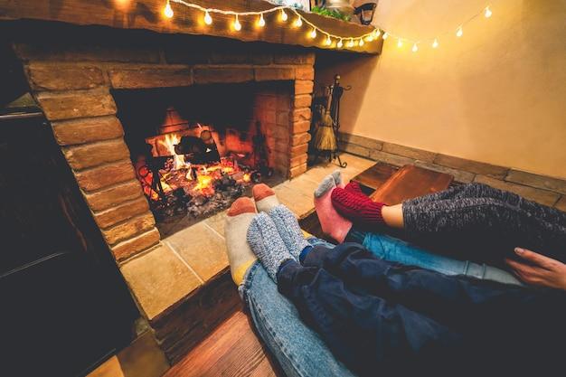 Widok nóg szczęśliwej rodziny leżącej obok kominka w ciepłych wełnianych skarpetkach
