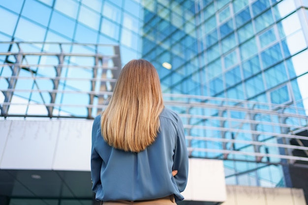 Widok odnoszącego sukcesy menedżera z tyłu, patrząc na biznesowy budynek nowoczesnego miasta.