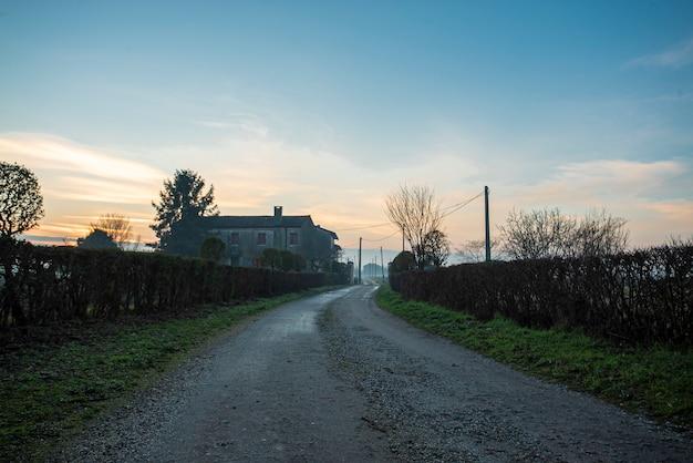 Widok ogólnej brudnej drogi w krajobrazie wiejskim w sezonie zimowym