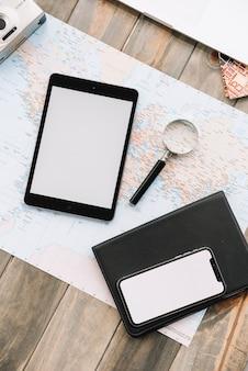 Widok ogólny cyfrowego tabletu; komórka; szkło powiększające i pamiętnik na mapie tle drewniane