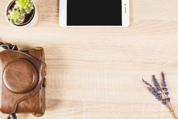 Widok ogólny telefonu komórkowego; doniczka z kaktusa; lawenda i aparat fotograficzny w etui na drewniane tła