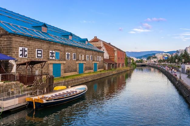 Widok otaru kanał z turystyczną łodzią i niebieskim niebem w lecie w otaru, hokkaido, japonia.