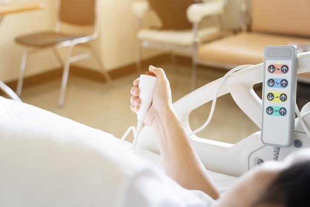 Widok pacjenta naciśnij czerwony przycisk awaryjny, aby zadzwonić do pielęgniarki o pomoc w szpitalu.