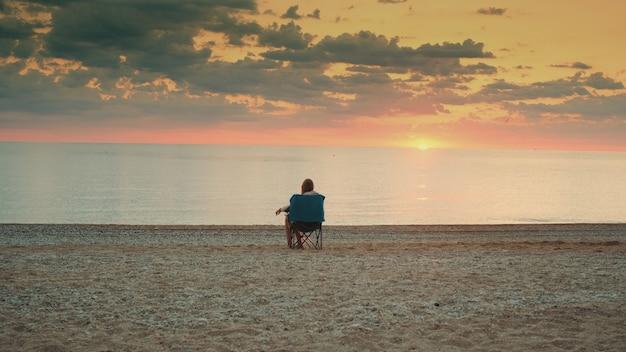 Widok pani podziwiającej zachód słońca nad morzem siedzącej w składanym fotelu turystycznym