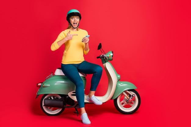 Widok pełnej długości ciała dziewczyny siedzącej na komórce bezpośredniego palca motoroweru