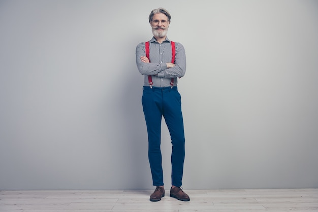 Widok pełnej długości ciała jego ładny atrakcyjny, dobrze ubrany modny wesoły wesoły mężczyzna stojący z założonymi rękami w klasycznym wyglądzie odizolowany na szarym tle ściany w pastelowym kolorze