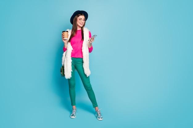 Widok pełnej długości ciała ładnej, atrakcyjnej, całkiem modnej, wesołej dziewczyny używającej urządzenia rozmawiającego z herbatą na jasnym, żywym połysku, żywy zielony niebieski turkusowy kolor ściany