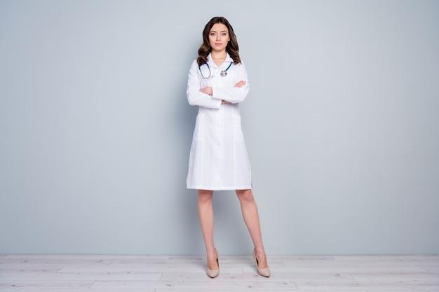 Widok pełnej długości ciała ładnej, atrakcyjnej, inteligentnej, sprytnej, doświadczonej, pewnej siebie, falistej dziewczyny doktor doktor z założonymi rękami medicare odizolowany na szarym tle w pastelowym kolorze