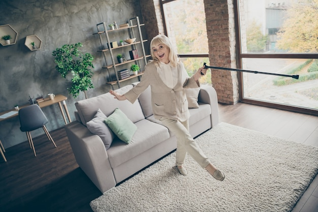 Widok pełnej długości ciała ładnej, atrakcyjnej, zdrowej, wesołej, radosnej, wesołej, siwowłosej babci tańczącej z laską, bawiącej się, styl życia w industrialnym ceglanym lofcie w nowoczesnym stylu