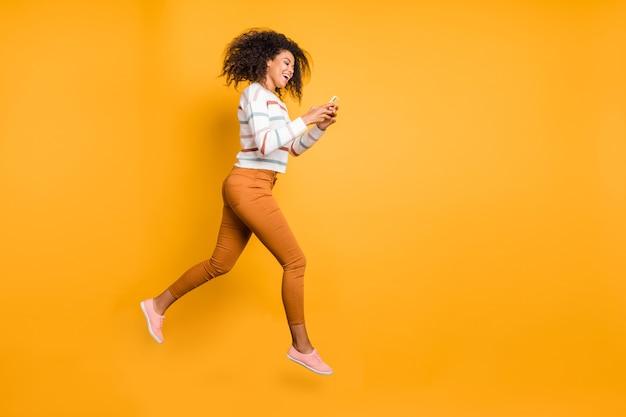 Widok pełnej długości ciała ładnej dziewczyny skaczącej za pomocą cyfrowego telefonu z aplikacją 5g