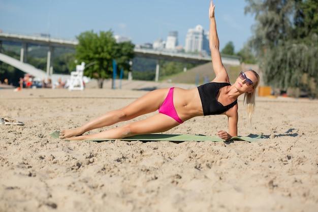 Widok pełnej długości muskularnej blondynki na bocznej pozycji deski na plaży