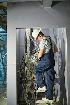 Widok pełnej długości z tyłu portret starszego elektryka łączącego kable w szafie z przewodami podczas remontu domu