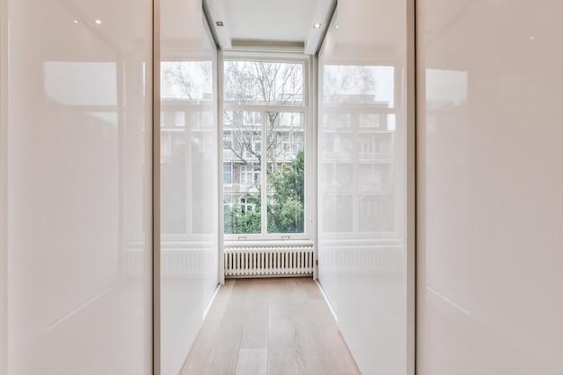 Widok perspektywiczny garderoby z błyszczącymi drzwiami przesuwnymi po obu stronach w stosunku do okna