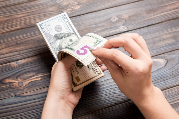 Widok perspektywiczny kobiet ręce liczenia pieniędzy. sto pięć banknotów dolarowych