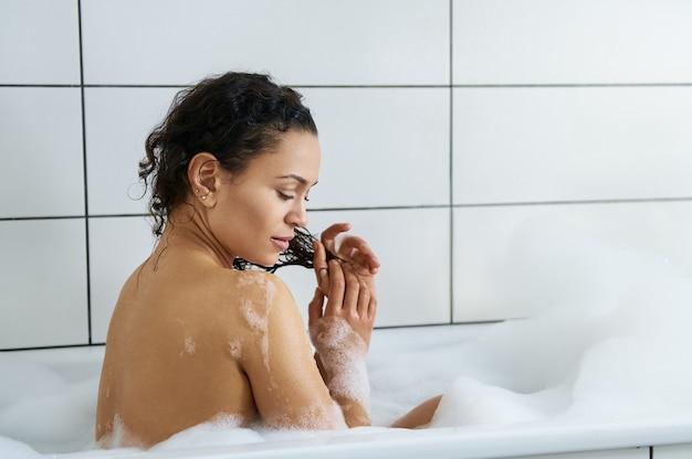 Widok pięknej kobiety relaksującej się w wannie i myjącej kręcone włosy
