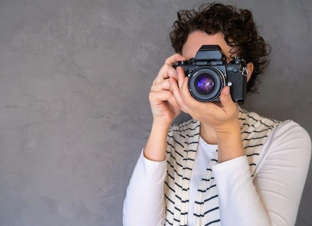 Widok pięknej kobiety robiącej zdjęcia profesjonalnym aparatem z miejsca na kopię.