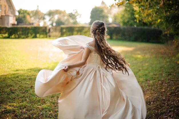 Widok pięknej narzeczonej przędzenia w sukni ślubnej z tyłu na zielonym polu w słoneczny dzień