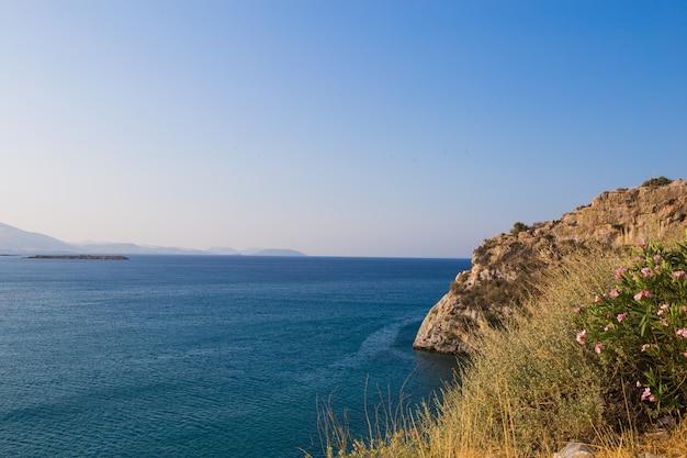 Widok pięknej plaży z czystą błękitną wodą, złotym piaskiem, kolorowymi łodziami i górami. letni krajobraz grecji i morza jońskiego.