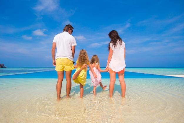 Widok pięknej rodziny z tyłu na plaży podczas letnich wakacji