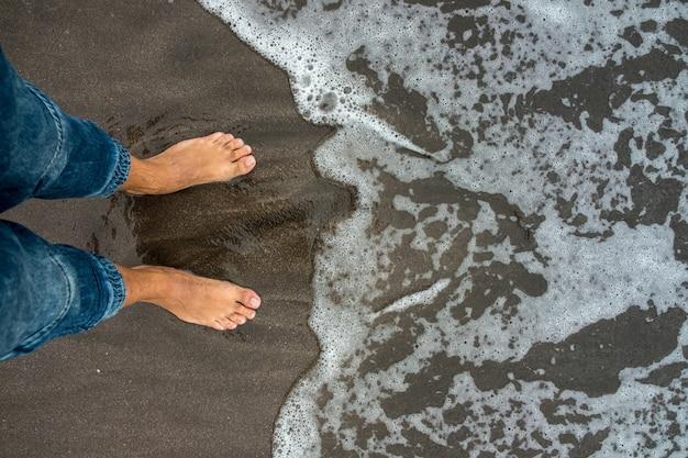 Widok pierwszej osoby na stopy na brzegu morza