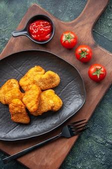 Widok pionowy bryłek kurczaka na czarnej tablicy i widelec na desce keczup pomidory na ciemnej powierzchni