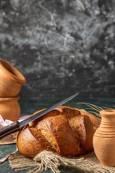Widok pionowy całego czarnego chleba na brązowych ręcznikach na ciemnej powierzchni