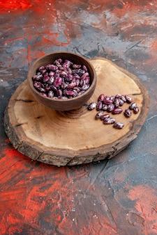 Widok pionowy czarnej fasoli puli instant w brązowej misce na drewnianej tacy na mieszanym kolorze tła
