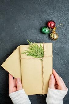 Widok pionowy dłoni trzymającej pudełka na prezenty i akcesoria do dekoracji na ciemnym tle