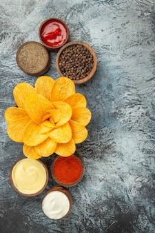 Widok pionowy domowych chipsów ziemniaczanych ozdobionych w kształcie kwiatu w brązowej misce na szarym tle
