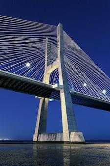 Widok pionowy mostu vasco da gama nocą, lizbona