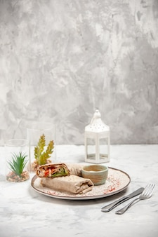 Widok pionowy okładu lawaszowego i jogurtu w małej misce na talerzu i sztućcach domu zabawek ustawionych na poplamionej białej powierzchni