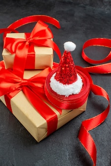 Widok pionowy pięknych prezentów z czerwoną wstążką i czapką mikołaja na ciemnym tle