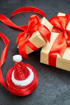 Widok pionowy pięknych prezentów z czerwoną wstążką i czapką świętego mikołaja na ciemnym stole