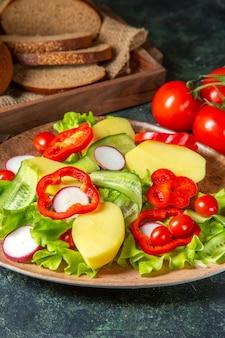 Widok pionowy pokrojonego świeżego czarnego chleba na ręcznik w brązowym drewnianym pudełku i posiekanych świeżych warzyw na talerzu na ciemnej powierzchni mix kolorów