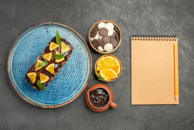 Widok pionowy pysznego ciasta ozdobionego cytryną i czekoladą z notatnikiem na ciemnym stole