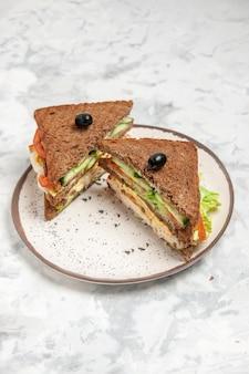 Widok pionowy pysznej kanapki z czarnym chlebem ozdobionym oliwką na talerzu na poplamionej białej powierzchni