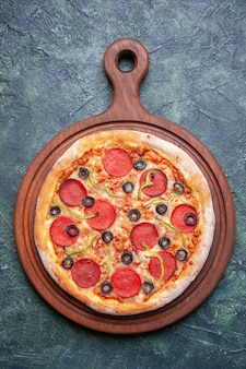 Widok pionowy pysznej pizzy na drewnianej desce do krojenia na ciemnoniebieskiej powierzchni