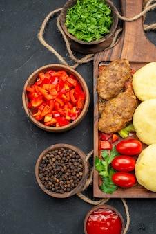 Widok pionowy smaczne kotlety posiekane warzywa na kolację w ciemności