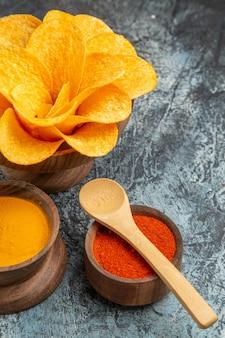 Widok pionowy smacznych chipsów ziemniaczanych ozdobionych różnymi przyprawami w kształcie kwiatów z łyżeczkami na szarym stole