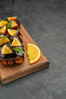Widok pionowy smacznych ciast ozdobionych cytryną i czekoladą na desce do krojenia na czarnym stole