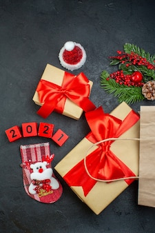 Widok pionowy świątecznego nastroju z pięknymi prezentami z czerwoną wstążką i numerami skarpety świętego mikołaja xsmas na ciemnym tle